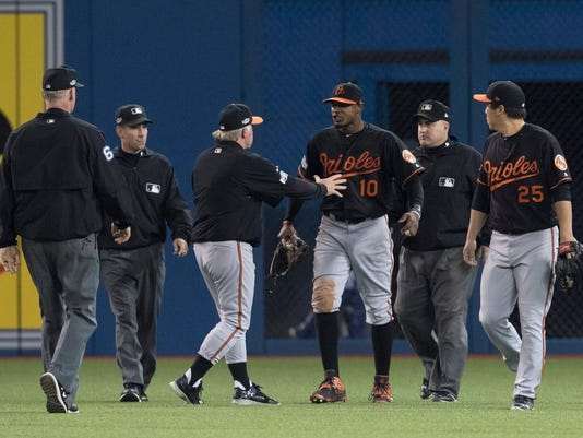 Umpires Ted Barrett, from left, David Rackley, Baltimore Orioles manager Buck Showalter, Orioles' Adam Jones, umpire Eric Cooper and Orioles' Hyun Soo Kim talk after a can was thrown onto the field during play following the seventh inning of an American League wild-card baseball game against the Toronto Blue Jays in Toronto, Tuesday, Oct. 4, 2016. (Mark Blinch/The Canadian Press via AP)
