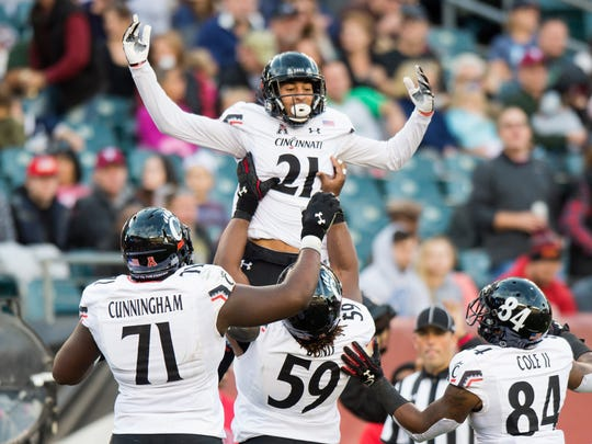 Cincinnati Bearcats wide receiver Devin Gray (21) celebrates his touchdown against the Temple Owls with offensive lineman Korey Cunningham (71) and offensive lineman Deyshawn Bond (59) and wide receiver Nate Cole (84) during the second quarter at Lincoln Financial Field.