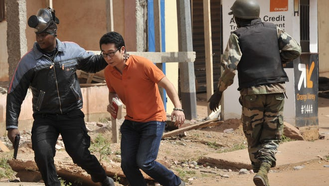 Malian security forces evacuate a man from an area surrounding a siege at the Radisson Blu hotel in the capital city, Bamako, on Nov. 20, 2015.