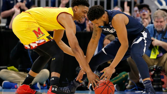 Maryland Terrapins forward Justin Jackson (21) and Xavier Musketeers guard Trevon Bluiett (5) fumble for a loose ball in the first half of the NCAA Tournament First Round game between the Maryland Terrapins and the Xavier Musketeers at the Amway Center in Orlando, Fla., on Thursday, March 16, 2017. At the half, Maryland led Xavier 36-35.
