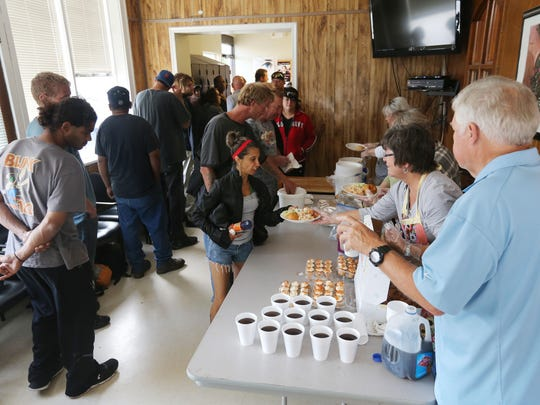 Volunteers from East Central Church of Christ serve lunch to people at Bill's Place. The building where the program is located has been put up for sale.