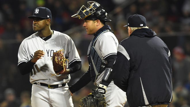 Apr 10, 2018; Boston, MA, USA; New York Yankees pitching coach Larry Rothschild (58) walks to the mound to talk with starting pitcher Luis Severino (40) and catcher Austin Romine (28) during the second inning against the Boston Red Sox at Fenway Park.