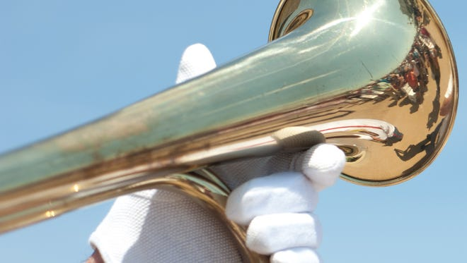 The crowd at the Bethany Beach Bandstand is reflected in a bugler's trumpet during Monday's Memorial Day services.