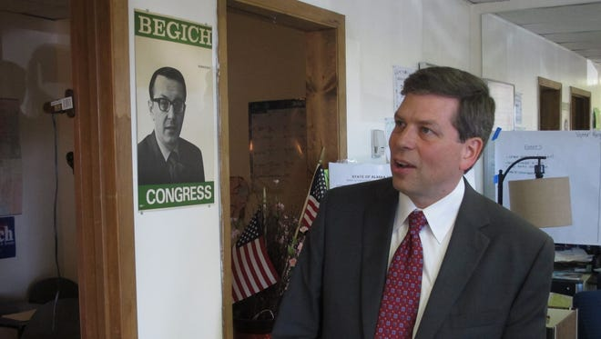 U.S. Sen. Mark Begich, D-Alaska, is shown in his campaign's volunteer office in Anchorage, Alaska, on Monday, Aug. 18, 2014, next to a campaign poster for his father, the late U.S. Rep. Nick Begich.