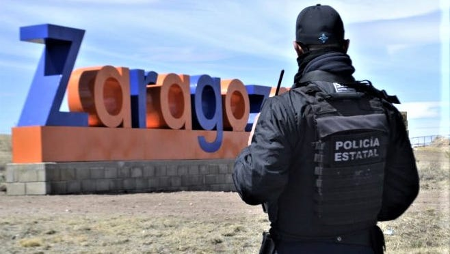 A Chihuahua state police officer stands watch by a sign for the town of Zaragoza after a political candidate and seven other people were killed in an attack.