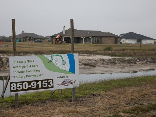 A sign advertising waterfront properties along a contributory to the Oso Creek Dec. 30, 2017.