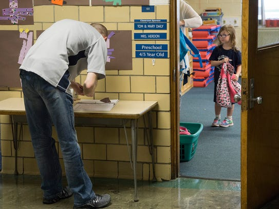 Brian Laramie checks daughter Avery Laramie, out of school for the day.