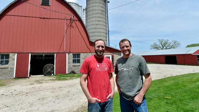 Ron, left, and Frank Henningfeld stand outside the barn at Romari Farm in rural East Troy. Ron uses some of Frank's milk for his cheesemaking company, Hill Valley Dairy.