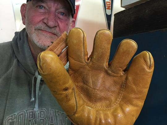 Bill Clews, owner of The New Hobby, tries on a 1940s era baseball glove that is believed to have been used by U.S. servicemen in the Pacific Theater during World War II.
