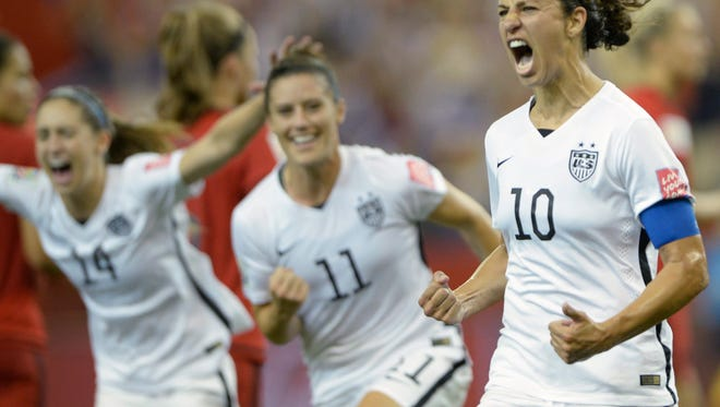 United States' Carli Lloyd (10) celebrates with teammates Ali Krieger (11) and Morgan Brian after scoring on a penalty kick against Germany during the second half of a semifinal in the Women's World Cup soccer tournament, Tuesday, June 30, 2015, in Montreal, Canada.