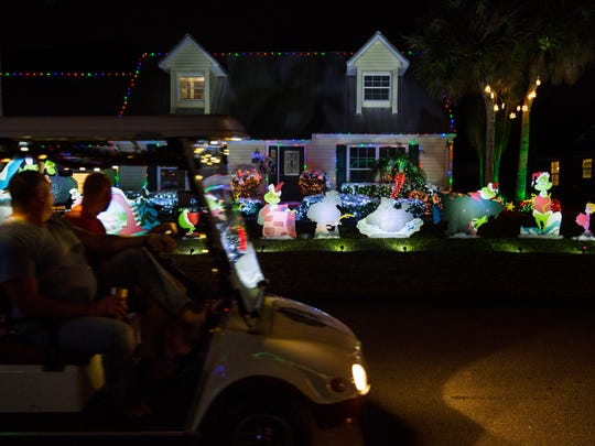 People ride a golf cart through the Victoria Park neighborhood to look at all the Christmas decorations on Thursday, Dec. 15, 2016.