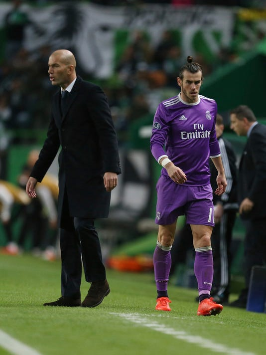 Real Madrid's Gareth Bale, right, leaves the pitch as head coach Zinedine Zidane gives directions to his payers during the Champions League Group F soccer match between Sporting CP and Real Madrid at the Alvalade stadium in Lisbon, Tuesday, Nov. 22, 2016. (AP Photo/Armando Franca)