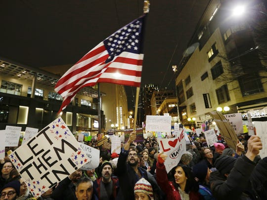 "In this Sunday, Jan. 29, 2017 photo, a protester waves a U.S. flag as another holds a sign that reads ""Let Them In"" during a march and rally to oppose President Donald Trump's executive order barring people from certain Muslim nations from entering the United States, in downtown Seattle."