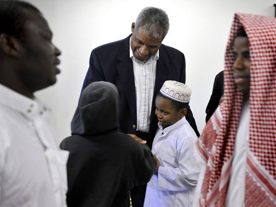 Imam Anthony Weatherspoon, center,   greets worshippers