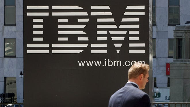 A pedestrian passes an IBM sign outside an IBM building May 10, 2005 in downtown Chicago.