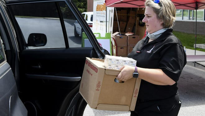 Amanda Govern loads a box of food into a vehicle at Innovative High Schools Sept. 4. Only Hope WNC and Olive Branch Food Pantry partnered with the school to hand out free meals and hygiene products to students and their families. Only Hope WNC was recently awarded a $5,000 grant for community food distribution.
