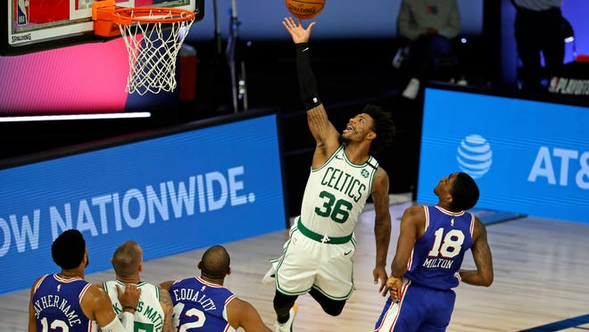 Boston Celtics guard Marcus Smart (36) attempts to shoot around around Philadelphia 76ers guard Shake Milton (18) during the first half of Game 3 of an NBA basketball first-round playoff series, Friday, Aug. 21, 2020, in Lake Buena Vista, Fla.