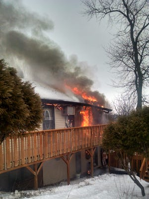 Flames escape the residence at 5231 Skyline Drive, Holiday lake, as Brooklyn and Hartwick volunteer firefighters fight the blaze on Thursday morning, Jan. 7.