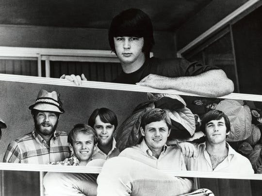 Brian Wilson holding a photo of the rest of the Beach