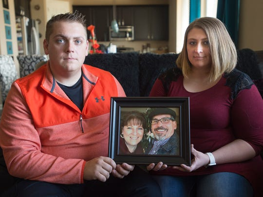 Colby Zander and Katie Byers hold a photo of their mother and father, Josh and Sherri Zander of Fort Collins, who died in a motorcycle crash west of Loveland last summer.