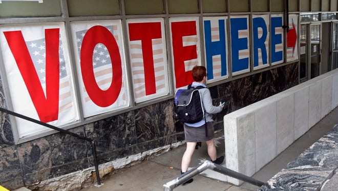 In this Sept. 23, 2016, file photo, a woman passes a large sign before voting in Minneapolis.