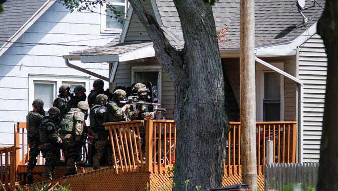 Members of the Michigan State Police tactical team head inside a home in the 200 block of Mifflin on Lansing's east side Friday afternoon, July 7, 2017, after a 14-hour standoff.   Officers had been on scene since 10:30 p.m. Thursday, seeking a man charged with felonious assault against his neighbor who reportedly was holed up inside the house.  No one was in the home upon entry.  [MATTHEW DAE SMITH/Lansing State Journal]