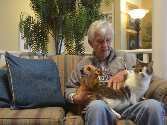 Whitney Conviser pets his dog Chiclet and community