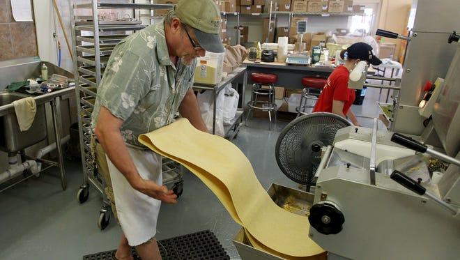 Jon Stadt, owner of Flour City Pasta, making lemon pepper pasta in his Fairport shop.