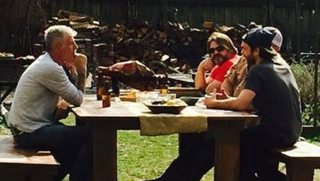 """Anthony Bourdain, left, talks with Tyler Brown (red shirt) Patrick Martin (white hat) and Tandy Wilson (dark hat) during a shooting for the CNN show """"Parts Unknown."""""""