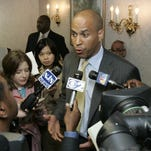 FILE: Cory Booker, center, talks with reporters during a stop at a senior citizen housing complex in Newark, N.J., Wednesday, May 10, 2006, the day after he was elected mayor of Newark. Booker says his overwhelming victory gives him a mandate to implement change in New Jersey's largest city. (AP Photo/Mike Derer)
