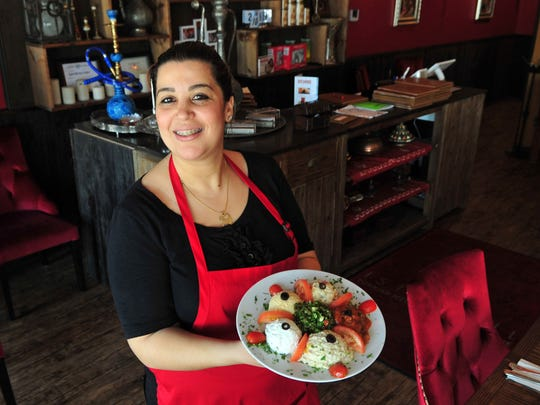 Samira Bourdrid holds the mixed appetizer includes hummus, baba ghanoush and laphne.