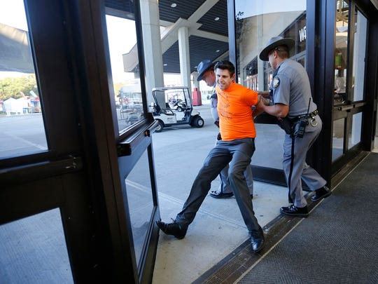 Chris Hartman of the Fairness Campaign is dragged by two Kentucky State troopers from the Kentucky Farm Bureau ham breakfast, at the state fair.  Hartman and others were there to protest the Kentucky Farm Bureau's hiring practices which the protestors consider to by anti-LGBT.  By Pat McDonogh, The Courier-Journal. Aug. 27, 2015.