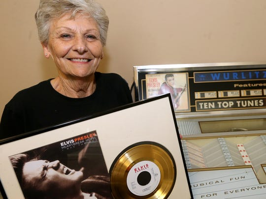 Pat Patterson stands beside her jukebox containing only Elvis music, on Thursday, Aug. 10 ,2017, as she holds up an Elvis Gold record that she purchased off of Ebay.