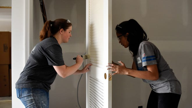 Jenna Crunk and Iman Huszainey, 16, paint a closet door as Habitat for Humanity of Greater Nashville hosts their first interfaith build day for Mohammad Abbas and Shelan Sinjo in Antioch, Tenn. on Sept. 17, 2016. Volunteers from First Presbyterian Church, The Temple in Nashville and the Islamic Center of Murfreesboro came together to help alongside staff from Habitat for Humanity.