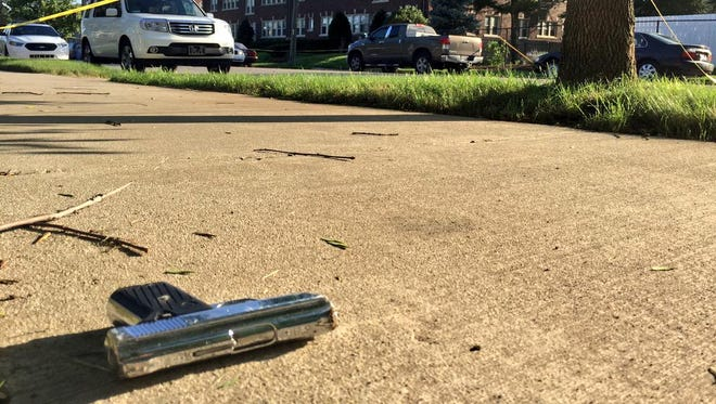 Police cordon off the area around a gun found near the shooting scene.