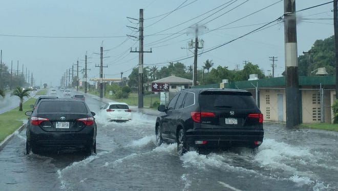 Flash flooding north-bound lane along Marine Corps Drive across from Guam Airport Hotel and Chief Brodie Memorial School, on July 30, 2017. At least one sedan is stuck on the flooded road.