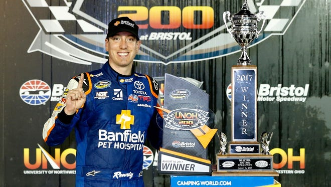 Kyle Busch celebrates in Victory Lane with the winners trophy after winning the NASCAR Camping World Truck UNOH 200 at Bristol Motor Speedway.