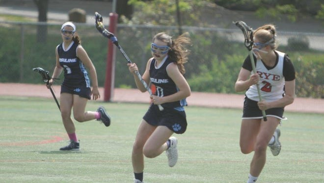 Senior midfielder Claire Fox, shown carrying the ball last year against Rye, is expected to be a major cog in Ursuline's offense this season.