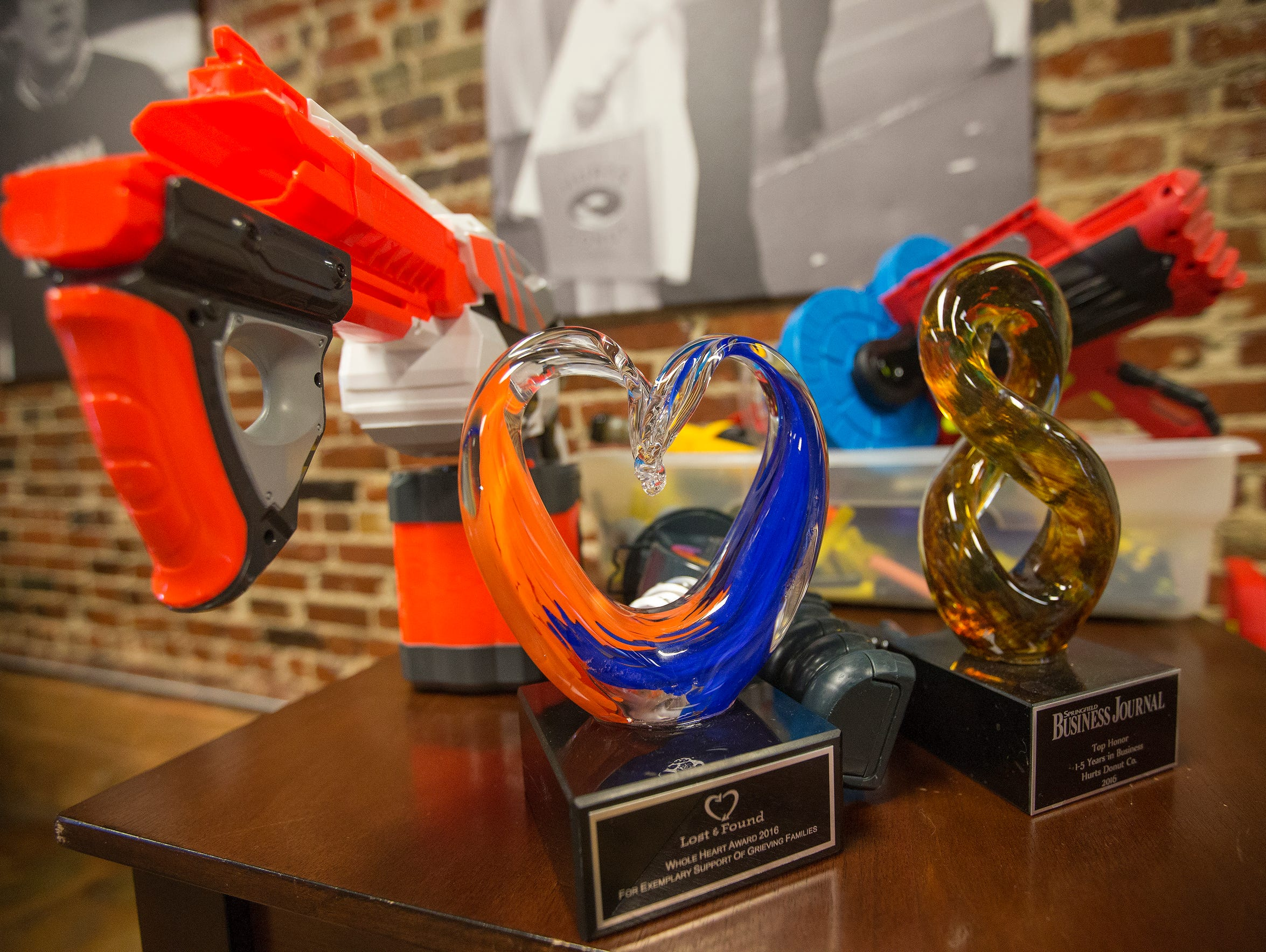 Nerf guns sit near a couple of awards at the Hurts