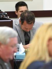 Defense attorney Albert Perez Jr. hangs his head as