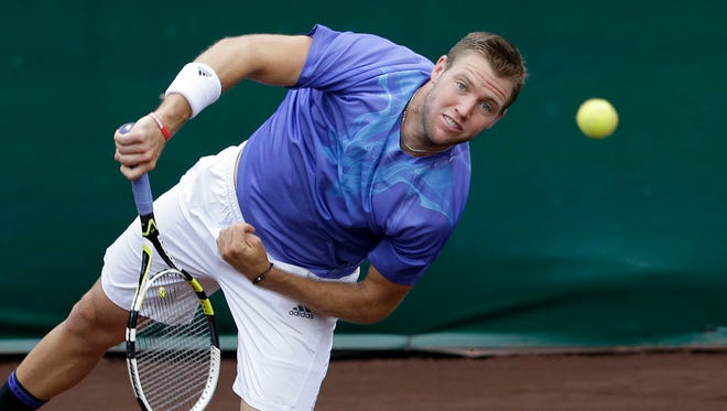 Jack Sock of the United States returns a shot to Kevin Anderson from South Africa in a semifinal match at the U.S. Men's Clay Court Championship.