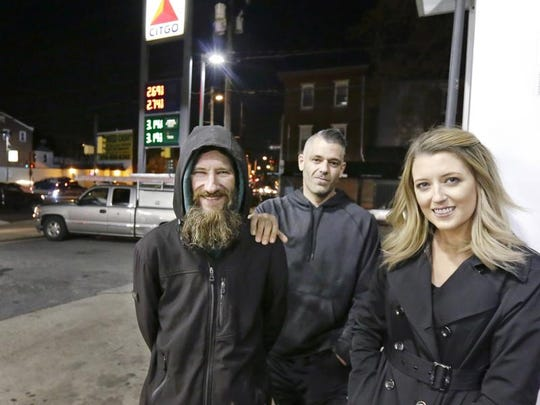 In this Nov. 17, 2017, photo, Johnny Bobbitt Jr. (left), Kate McClure (right) and McClure's boyfriend, Mark D'Amico, pose at a Citgo station in Philadelphia.