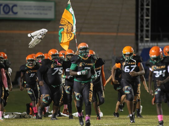 The FAMU DRS football team runs onto the field during