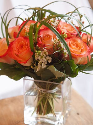 High and Magic by Darling Flowers consists of orange crush roses and grass leaves. It is one of the most popular bouquets they sell.
