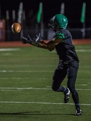 Farmington's Axel Fowler catches a pass against Roswell on Friday at Hutchison Stadium.