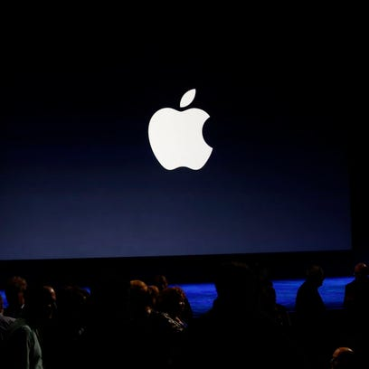 An Apple logo is seen on screen from the stage ahead