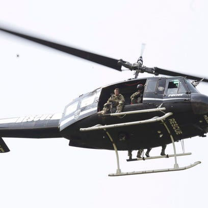 A police helicopter patrols a swampy area near route