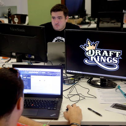 FILE - In this Sept. 9, 2015, file photo, Len Don Diego, marketing manager for content at DraftKings, a daily fantasy sports company, works at his station at the company's offices in Boston. The daily fantasy sports industry is eyeing a breakout season as NFL games begin. And its two dominant companies, DraftKings and FanDuel, are touting lucrative opening week prizes to try to draw more customers as more competitors pop up. (AP Photo/Stephan Savoia, File)