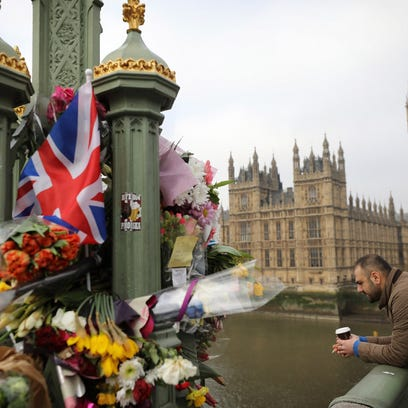 Flowers are left on Westminster Bridge by the Houses