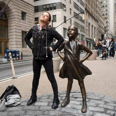 A woman strikes a pose in front of a statue titled